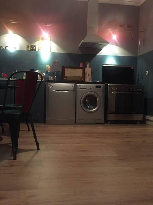 Grande cuisine, parquet au sol, avec grande fenetre donnant au Sud