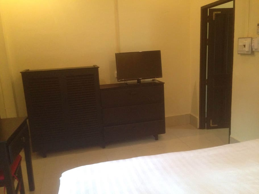 The bedroom includes a new, flat-screen TV and Lao furniture.