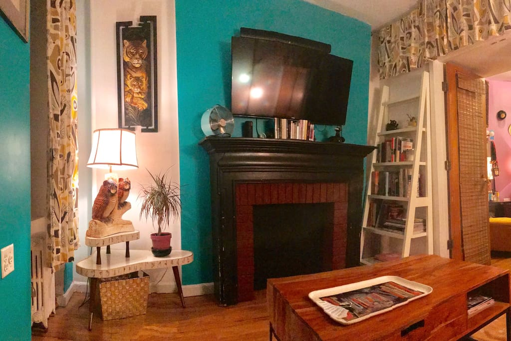 Living room with Smart TV/Netflix/Hulu etc, decorative fireplace, and charming mid century style furnishings.