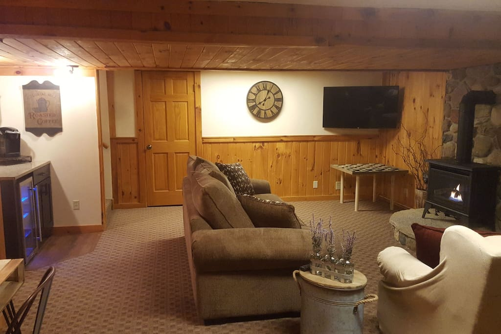 Living area - tv, coffee bar with beverage cooler, desk and gas wood stove. privacy door at the top of stairwell. Bluetooth speaker on desk.
