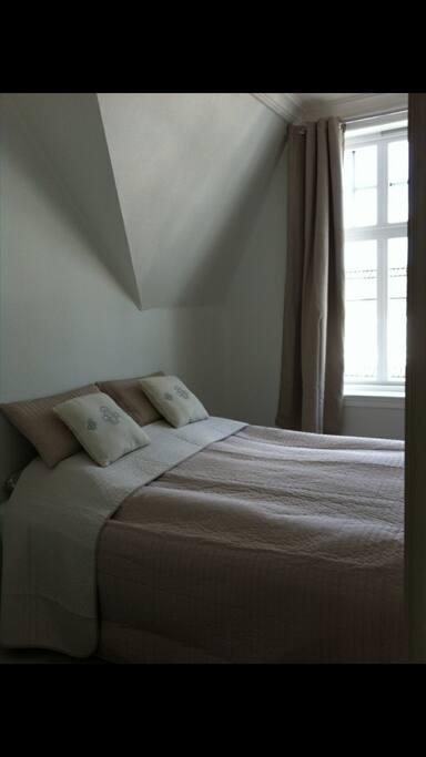 Soverom med dobbeltseng. Her er noe utsikt mot Fløyen. Bedroom with a queenbed.
