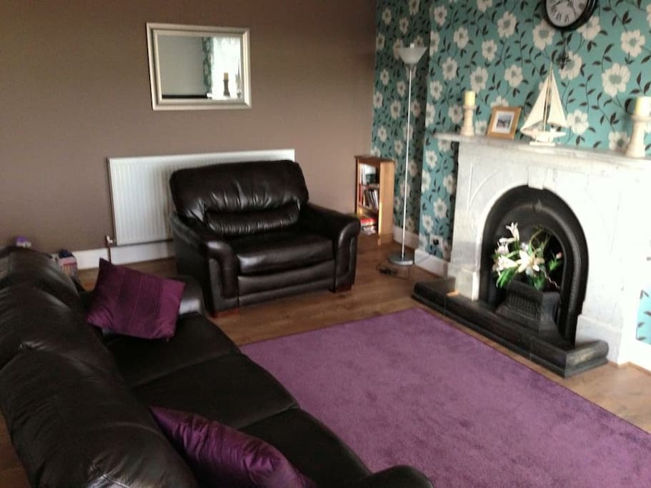 Comfortable Spacious lounge with high Victorian ceiling and original fire place which is now ornamental. TV and DVD player with selection of DVDs