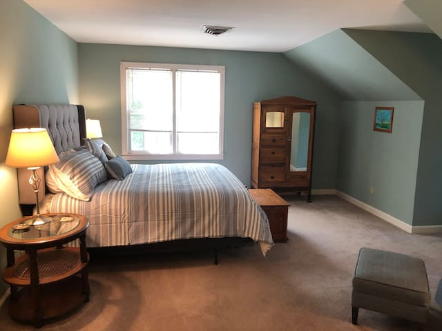 The large upstairs master bedroom is bright and welcoming, featuring a sitting area and an en suite half bath.