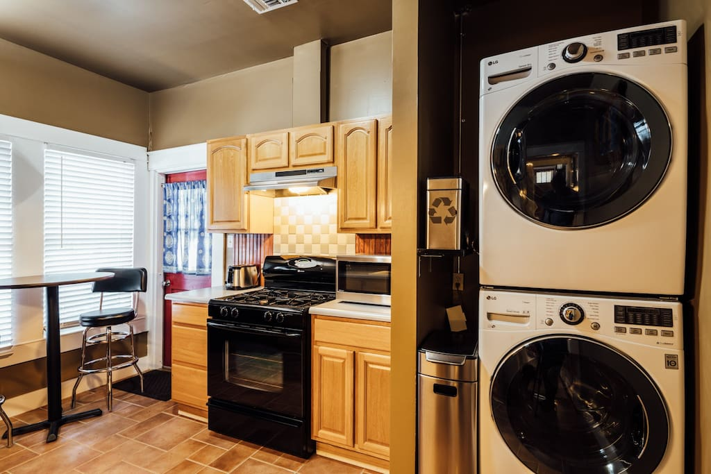 Kitchen with full size washer & dryer, gas cooking and a table for two.