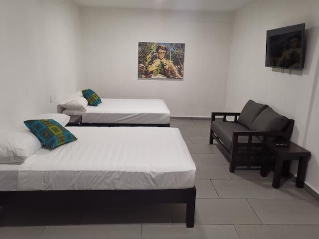 Habitación con dos camas matrimoniales, sofá, escritorio, smart tv, closet y baño privado dentro de la habitación.