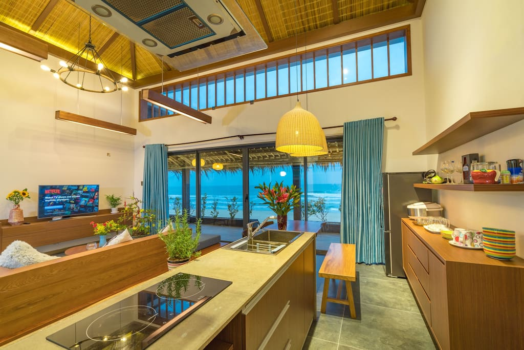 the opened living room and kitchen facing up to the beach