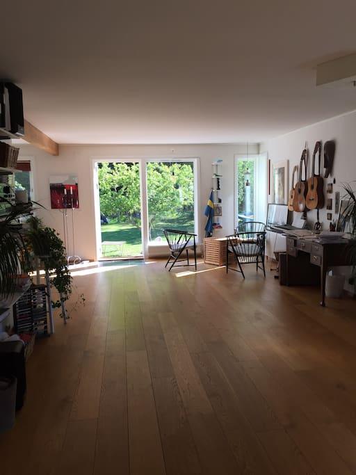 vardagsrum med dörr ut till altan och trädgård