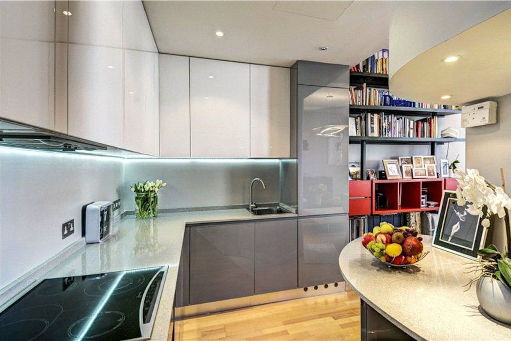 Designer Kitchen, recently fitted, with combi oven, integrated washing/ drying machine and integrated dish washer. High gloss thick doors and stone worktop.