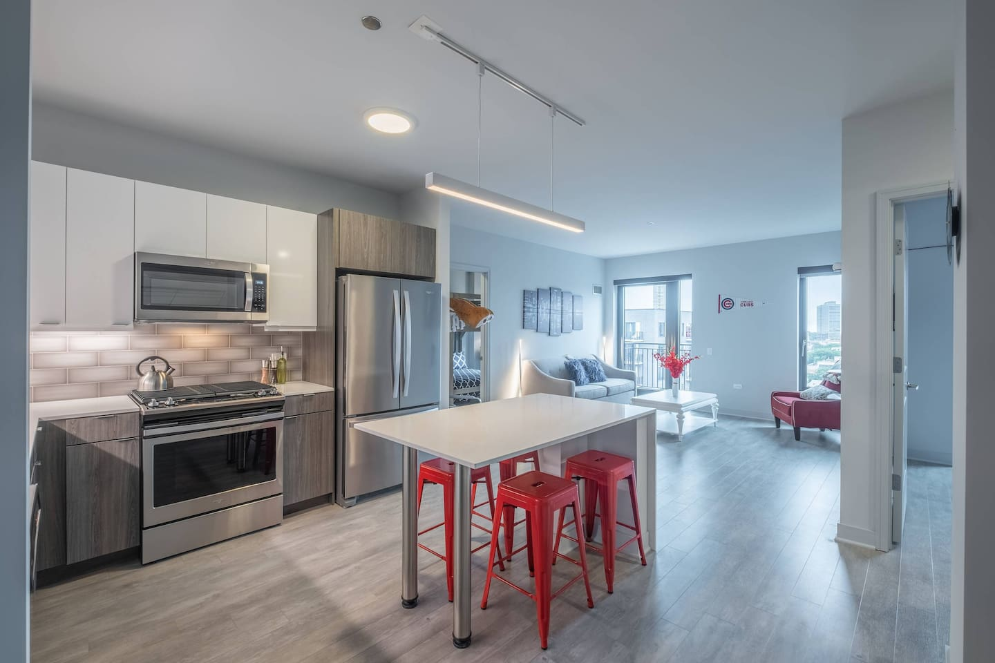 Kitchen offers stainless steel Whirlpool appliances including dishwasher and gas range, full tile back splashes, quartz countertop island barstool seating as well as table seating