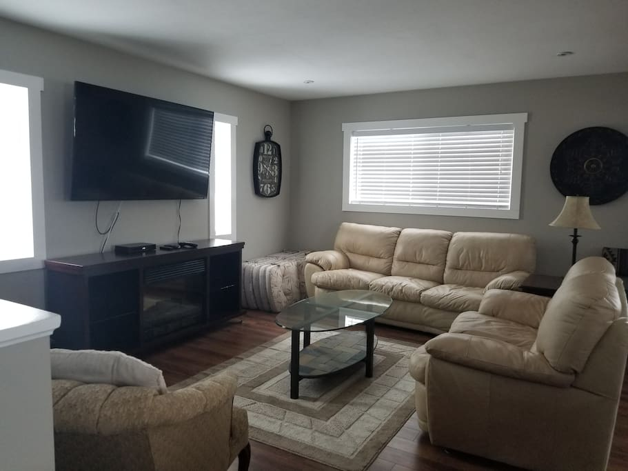 "Living Room with leather sofas, 60"" TV with Shaw Cable and internet included"