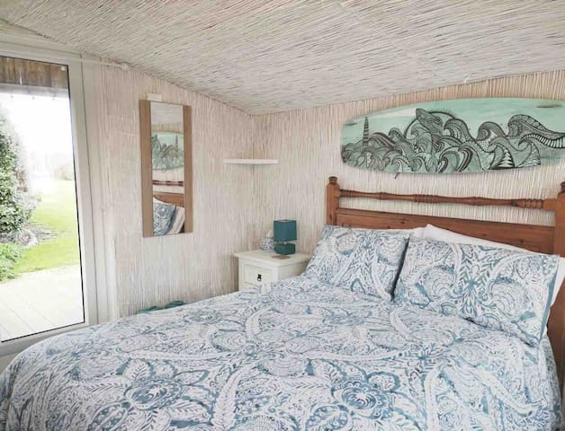 The bedroom has a comfortable double bed with doors that lead out to the front decked veranda & large garden with views to the sea & wonderful sunsets.