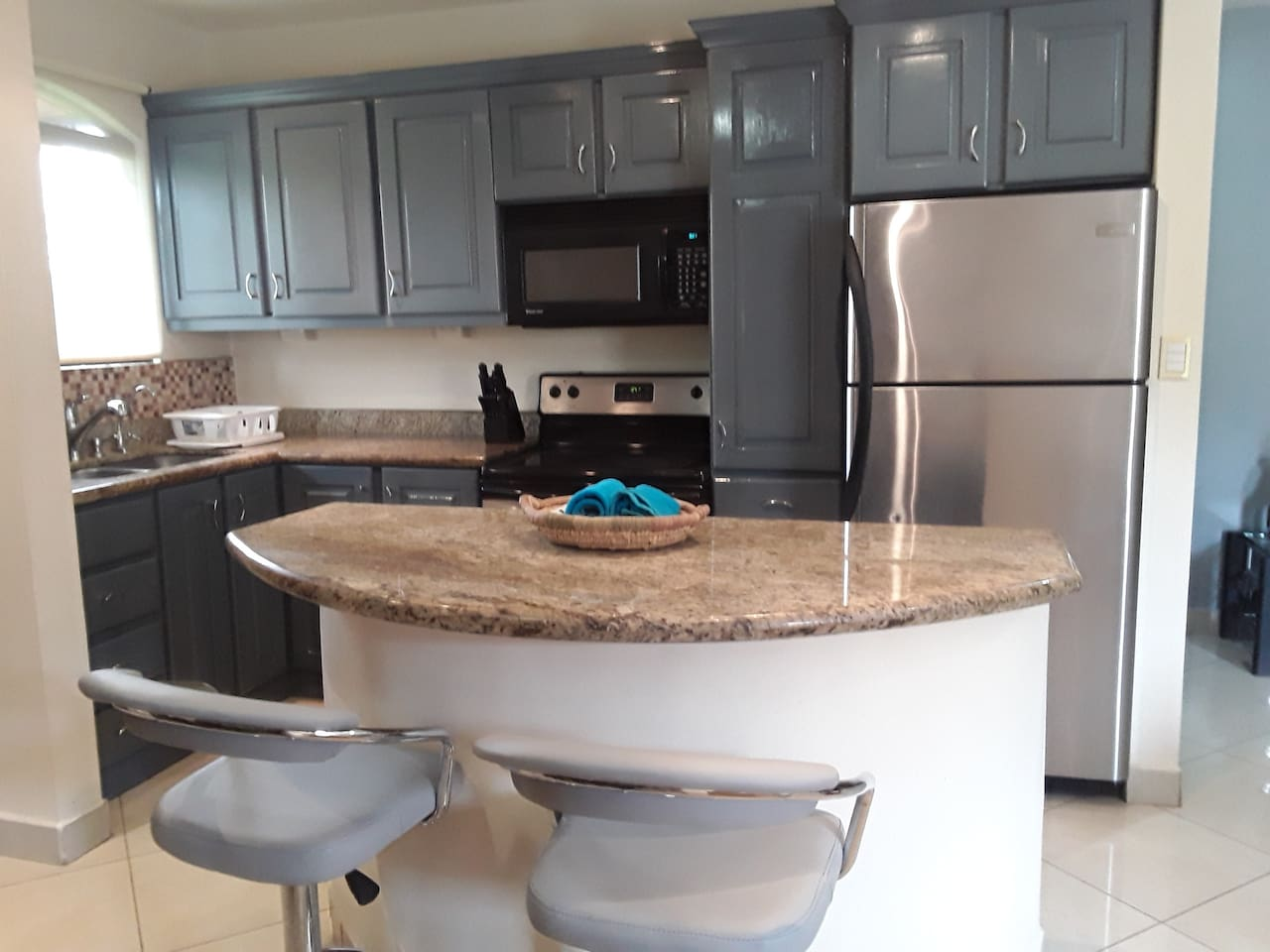 Kitchen with island, microwave, fridge, stove, blender, rice maker, coffee maker