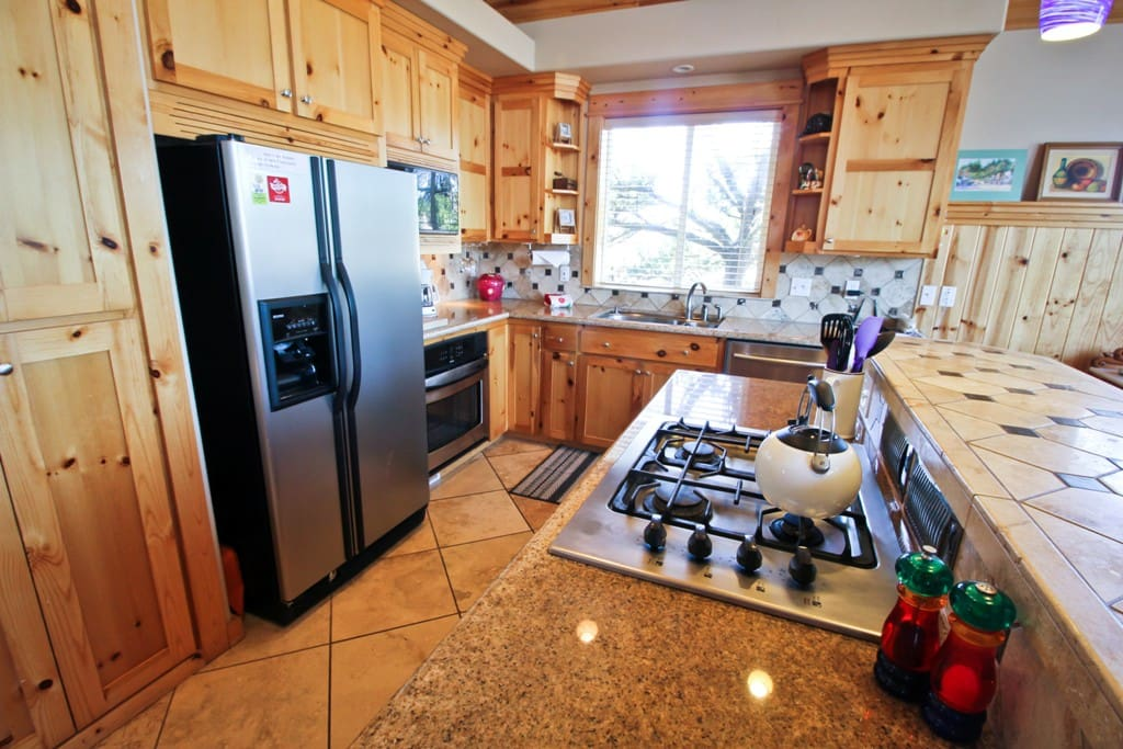 Middle level fully equipped kitchen with stainless steel appliances, granite counter tops, gas cook stove, toaster oven and a breakfast bar for 3