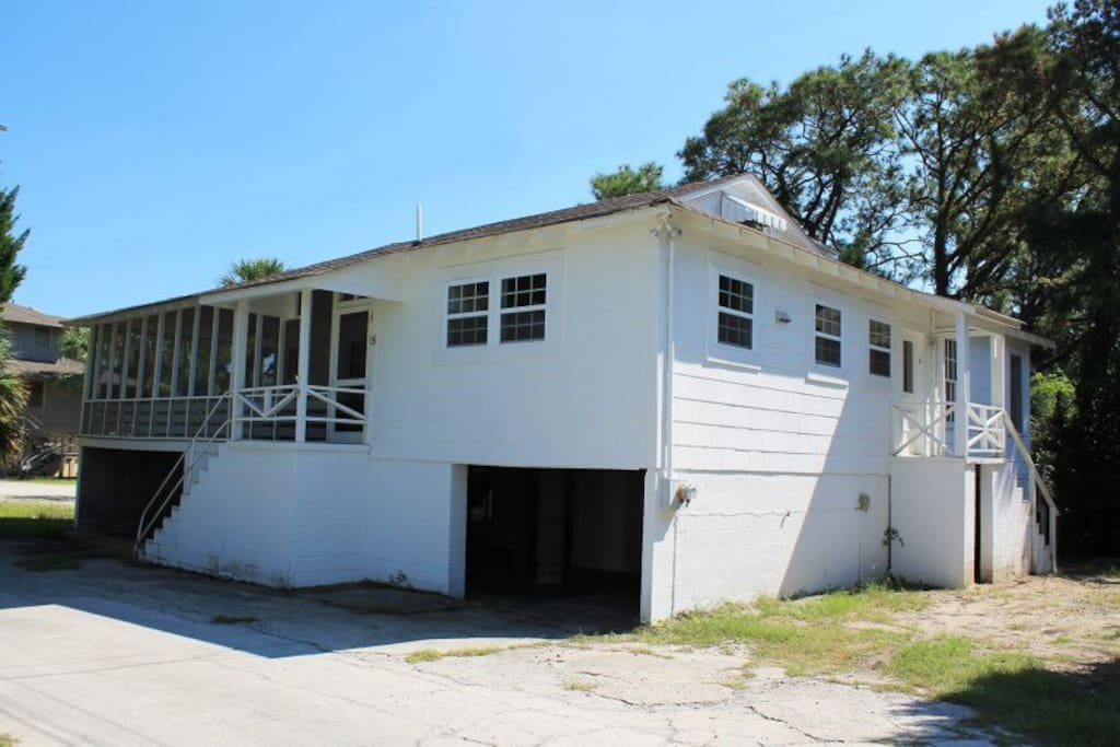 This classic Tybee cottage features a large wrap-around screened porch to enjoy the ocean breezes and sounds of the surf