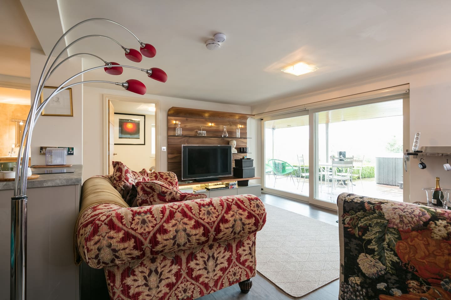 View of sitting room with two oversize comfy sofas, large screen television, and view out into garden and patio.