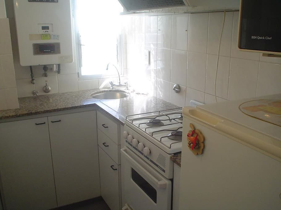 Comoda cocina con microondas, heladera y equipada con utencillos de cocina.