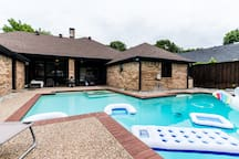 big pool with large sitting area  springboard tanning beds  barbecue area  3 Bluetooth speakers  small fridge