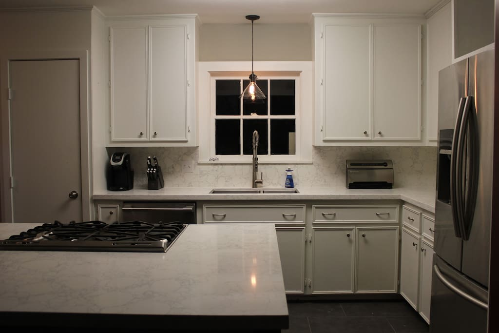 Chef's Kitchen-Recently remodeled luxury kitchen with beautiful quartz cabinets, large island open to dining room, and high end appliances. Over looks the back deck.