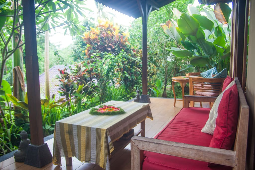 Chairs and table on the veranda with view over the jungle