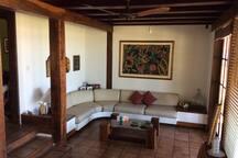 Ampla sala de estar com dois ambientes integrada à sala de jantar e com vista para o mar .