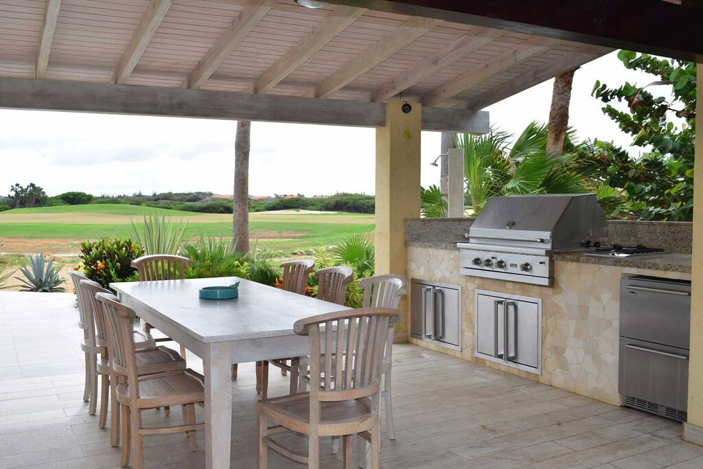 Terrace with 8-seat dining table and outdoor kitchen with large BBQ-grill