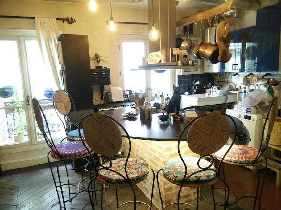 Séjour / cuisine que vous partagez avec nous. Grande table en forme d'escargot dessinée par moi. Casseroles en cuivres pour vous muscler.