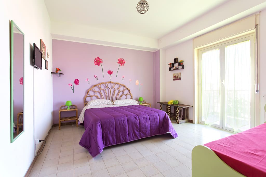 The violet bedroom with a double bed and a single bed.