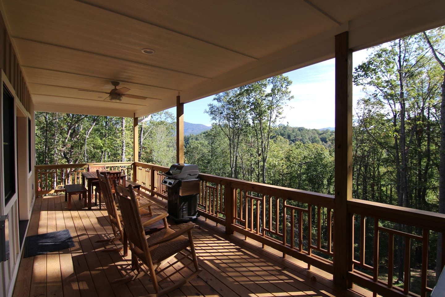 The back deck off the main level with dining table, grill, two rocking chairs and a hot tub.