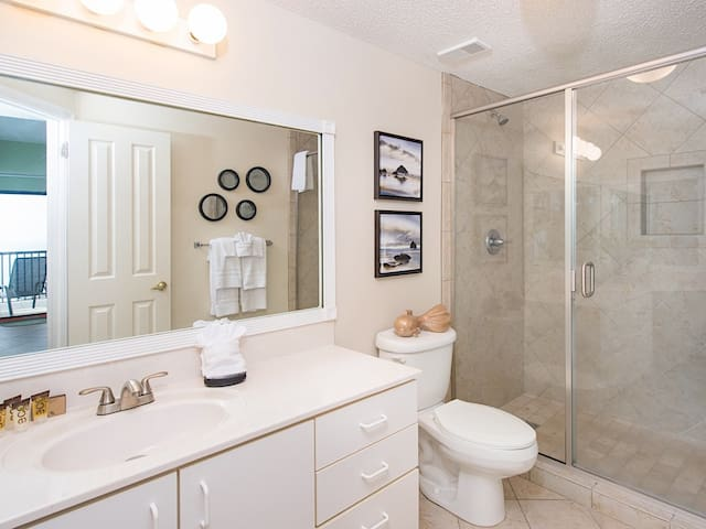 The master en-suite bathroom has a marble vanity and a walk-in shower.