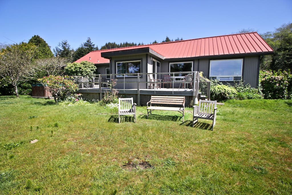 Back of house with large grassy yard, dual sided deck and hot tub, all with spectacular bay views!