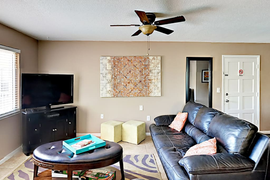 The living room offers seating on the leather couch