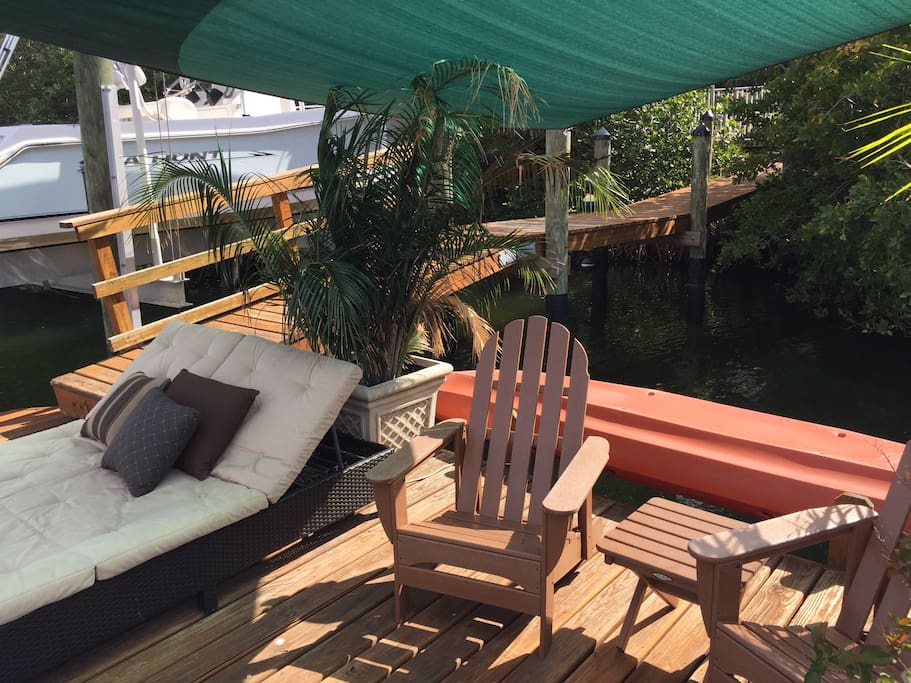 Floating dock with several chairs, double chaise lounger.