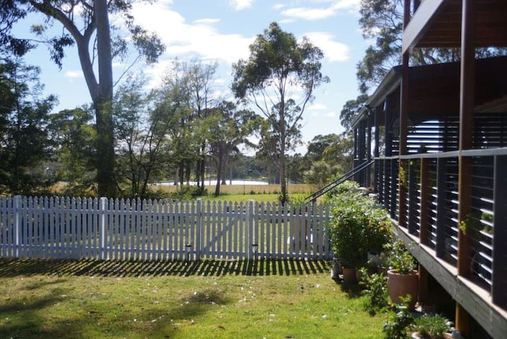 Looking East: entry gate to main cottage and view towards large neighbouring dam beyond