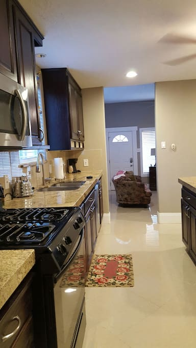 Kitchen with stainless appliances and a large granite center island & breakfast bar