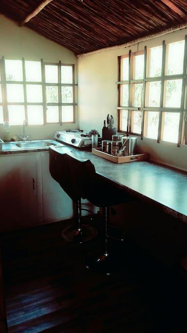 Kitchenette: Fridge, gas stove, cutlery & crockery, basin, chairs.