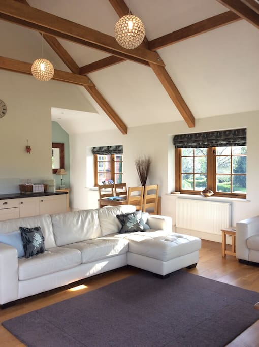 Open plan living with double height ceilings and oak floorboards.