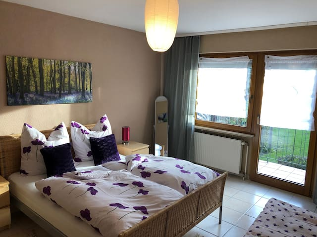 Doppelbett und ein Einzelbett im Schlafzimmer und ein kleiner Balkon mit Aussicht in den Garten.