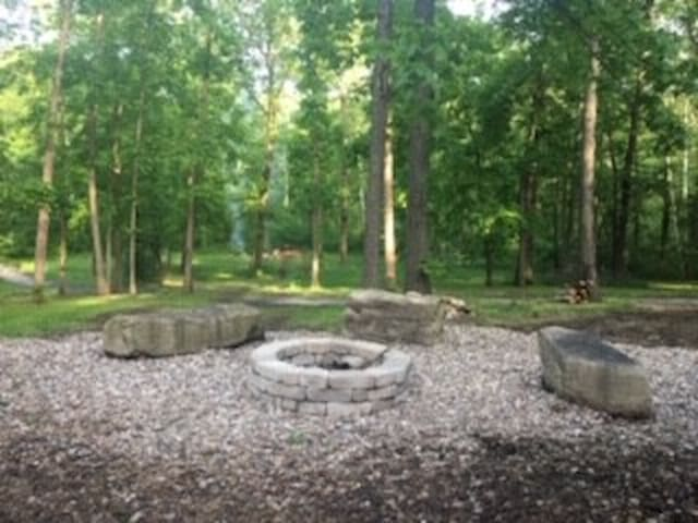 Fire pit beside the outdoor fireplace and BBQ grill. Firewood provided.