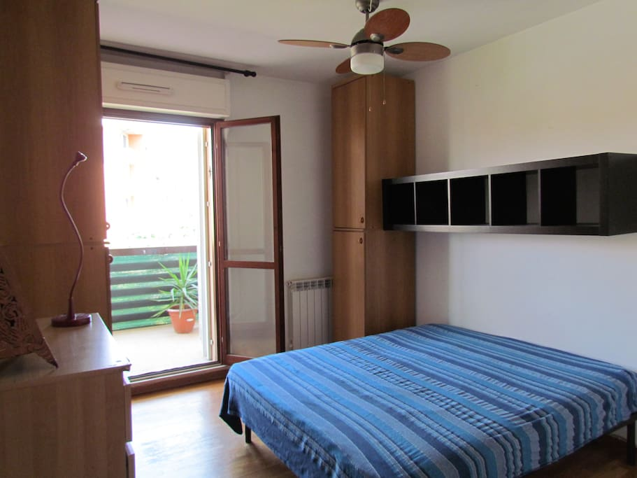 Bedroom with fan and balcony access.