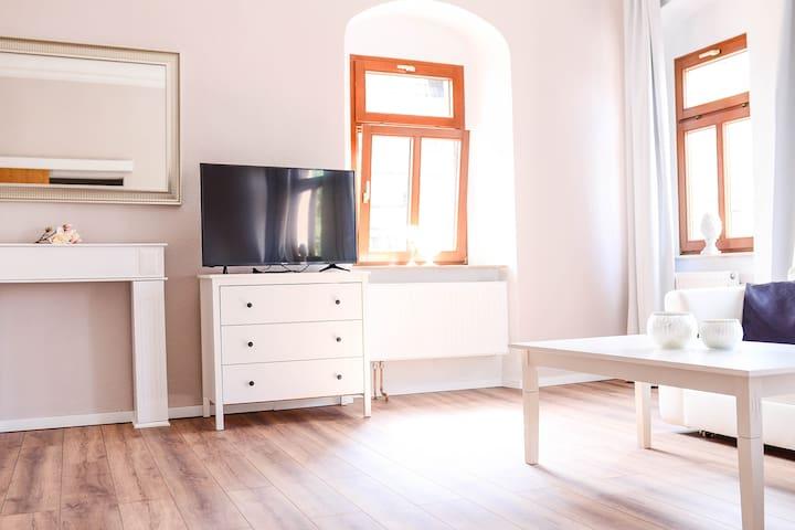 helles Wohnzimmer mit Stuckdecke