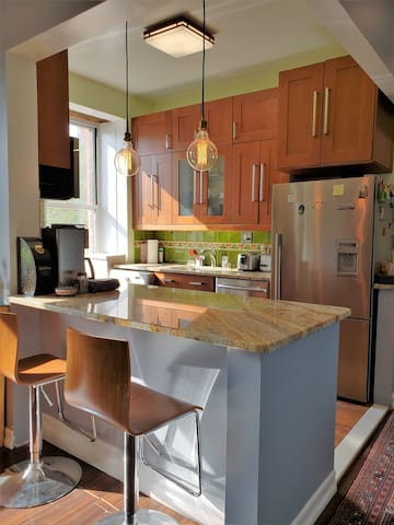 Open kitchen with granite countertops and seating for 2 people