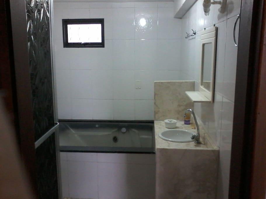 Banheiro estilo moderno com box e hidromassagem Jacuzzi.