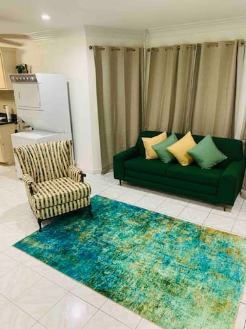 """A beautiful and vibrant open floor concept awaits you as you enter  """"Bella Vida""""!    Choose between allowing in the bright sunshine from the bay window area or enjoy solace from the black out curtains, as the emerald green sofa transforms into a bed."""