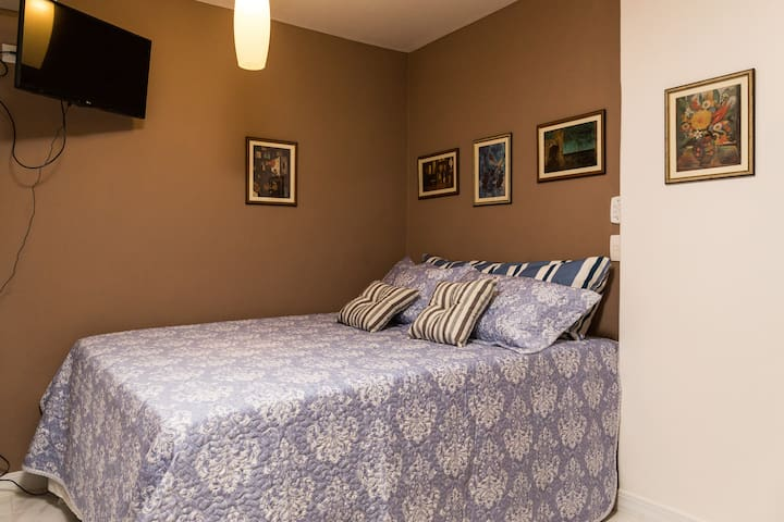 Cama queen size com roupa de cama de excelente qualidade e bom gosto.