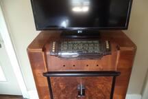Flat screen sit on vintage 30s radio console.