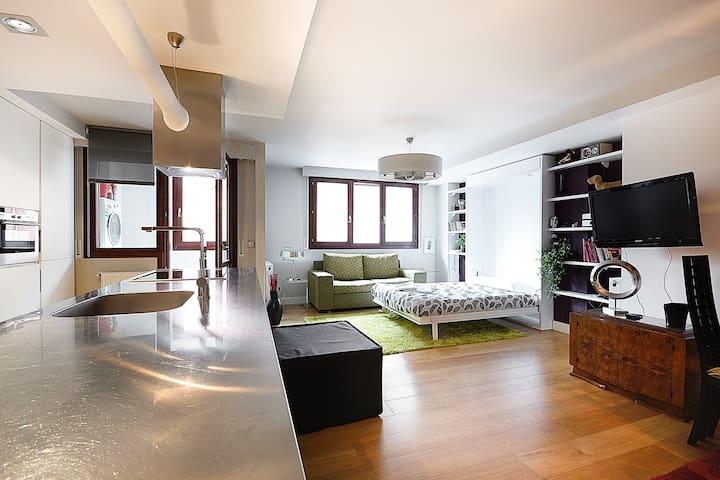 salón y zona de estar. cuenta con sofa y una cama que va en la pared que se baja cuando hace falta.