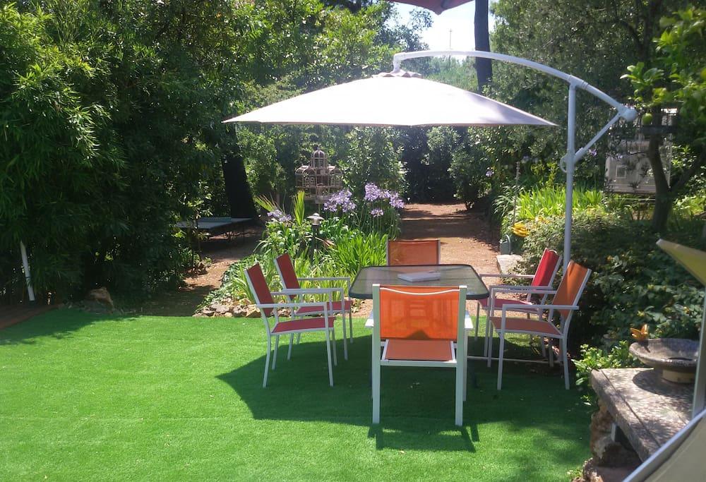 L'espace repas et derrière, au fond du jardin,  le jeu de boules.