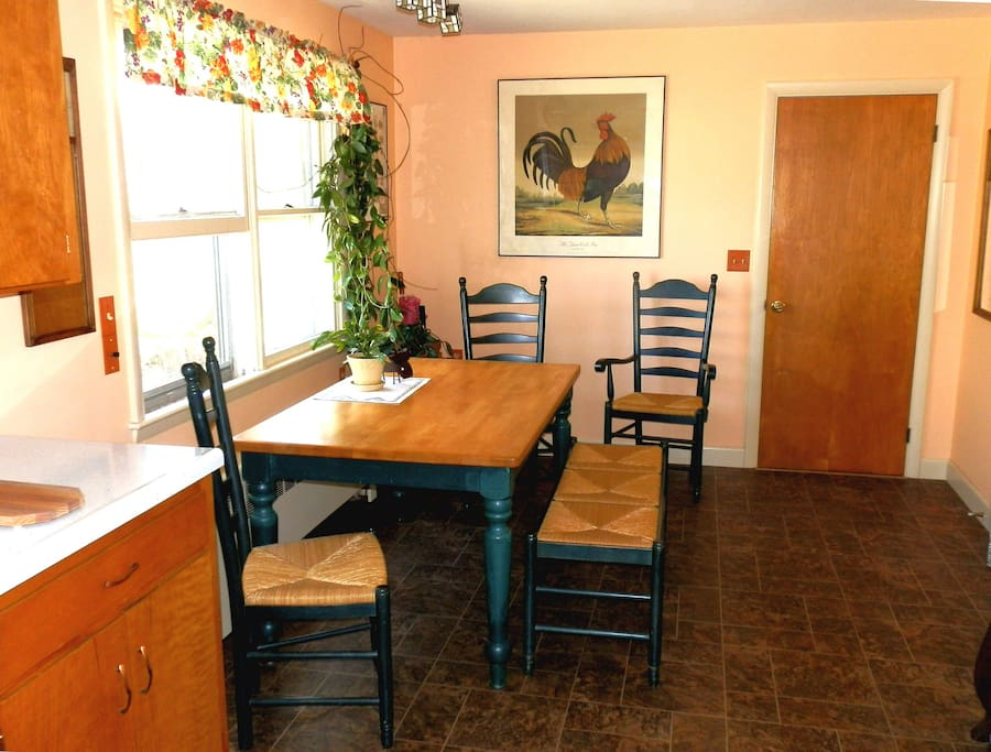 A big kitchen with room for six around the table with woven seat high back chairs and bench.