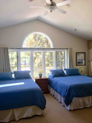 Second floor vaulted bedroom with two queen beds, skylight, ceiling fan and air conditioner.