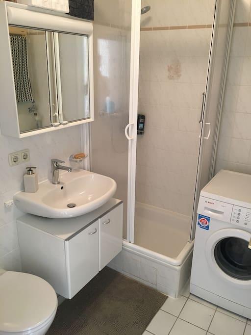 Badezimmer mit Dusche, Toilette und Waschmaschine